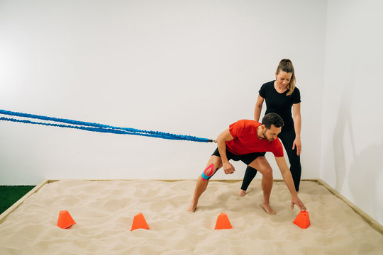 Physical therapist girl dressed in black clothes assists a male patient while doing a stretching exercise with a blue support on her leg on sand and small orange cones.