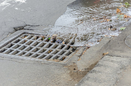 Water drains into a storm drain on the road close-up