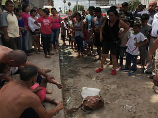 A Honduran girl is resuscitated on the banks of the Rio Grande where she had been bathing in Matamoros
