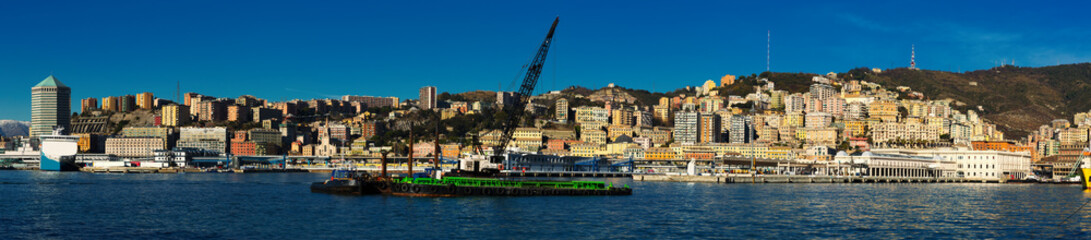 Old port of Genova city with cargo boats with crane at quay