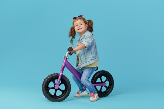 Little girl learns to keep balance while riding a bicycle. Stylish child in sunglasses  isolated on blue background
