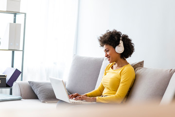 Smiling young woman with headphones using laptop in livingroom. Female studying at home. Young woman wearing headphones listens online web free audio course at home