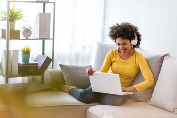 Young beautiful african american woman relaxing and listening to music using headphones. Smiling young woman watching a video with her laptop while siting on a sofa
