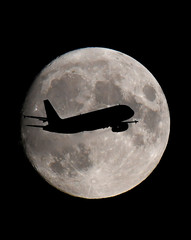 A passenger plane passes in front of the moon as it makes its final landing approach to Heathrow Airport in London