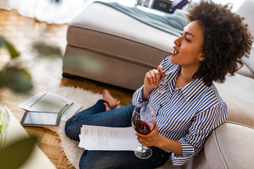 Just inspired. Confident young beautiful woman holding glass of wine and smiling while sitting on the floor at home with blueprint laying near her. Young business woman at home with notebook