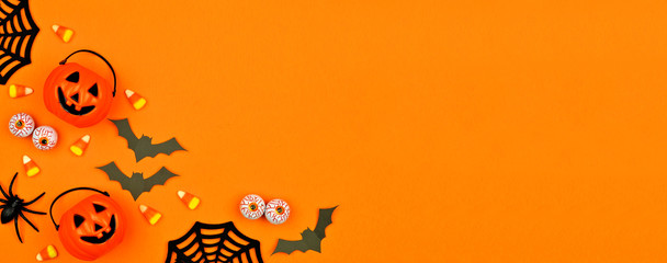 Halloween corner border banner with scattered candy and decor. Flat lay over an orange background with copy space.