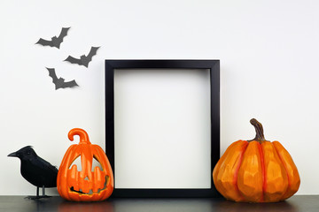 Mock up black frame with Jack o Lantern, pumpkin and crow decor on a shelf or desk. Halloween concept. Portrait frame against a white wall with bats.