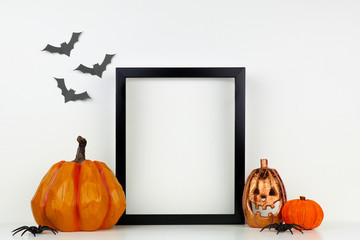 Mock up black frame with Jack o Lantern and pumpkin decor on a shelf or desk. Halloween concept. Portrait frame against a white wall with bats.
