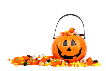 Halloween Jack o Lantern bucket overflowing with candy, side view isolated on a white background Wall mural