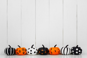 Black, white and orange patterned Halloween pumpkins in a row against a white wood background. Copy space.