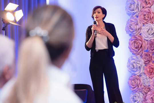 Beautiful business woman with microphone in her hand speaking at the  conference or seminar.