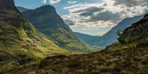 View of valley in Glencoe Scotland in morning with shadows and road snaking through to lake in distance