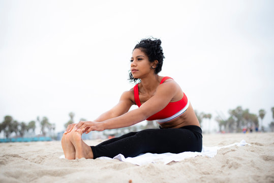 Physically fit latina stretches on the beach before working out