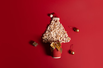 Christmas tree shaped popcorn on a red background. View from above. Flat layer