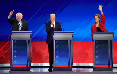 Former Vice President Joe Biden stands between Senator Bernie Sanders and Senator Elizabeth Warren as they both raise their hands to answer a question at the 2020 Democratic U.S. presidential debate in Houston