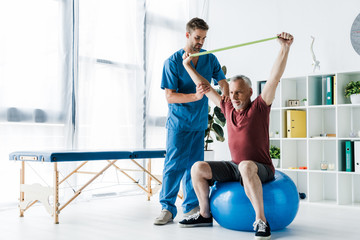 doctor standing near middle aged man exercising with resistance band while sitting on fitness ball