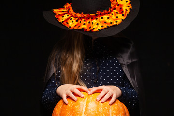 Halloween Witch with Pumpkin on black background. Beautiful young surprised woman in witches hat and costume holding pumpkin. Wide Halloween party art design. Copy-paste. Witch craft concept. Spider