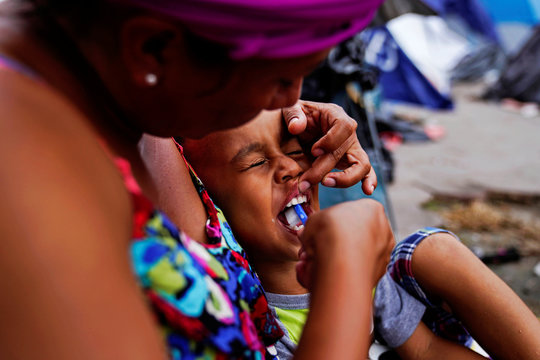 Honduran asylum seeker Francisca brushes the teeth of her son Nemihas, 4, in an encampment where they live at near the Gateway International Bridge in Matamoros, Mexico