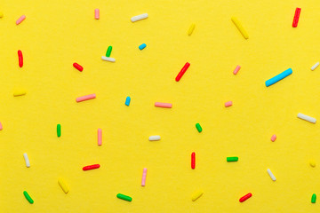 сlose up of colorful sprinkles over yellow background, decoration for festive Valentines day, birthday, holiday and party time