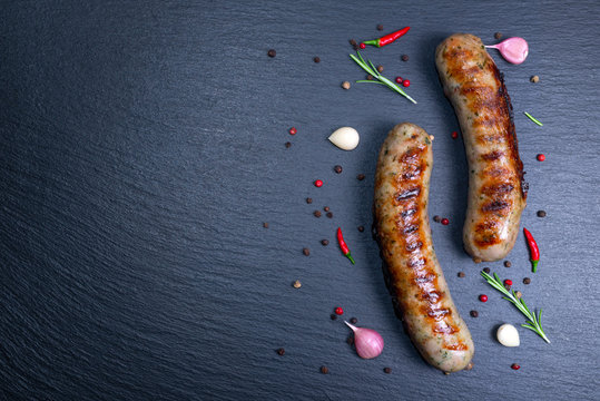 top view of grilled sausages decorated with chili and dry pepper, garlic, rosemary on black slate, copy space