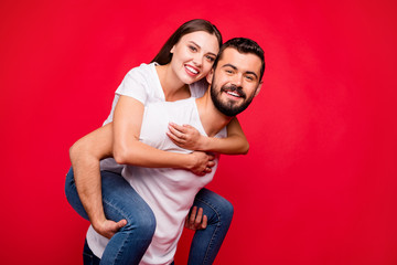 Photo of cheerful cute nice attractive trendy piggyback beautiful handsome couple wearing jeans denim while isolated with red background