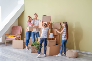 Happy family with belongings in their new house