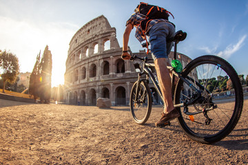 Happy young man tourist with bike wearing shirt and hat at colosseum in Rome, Italy at sunrise.