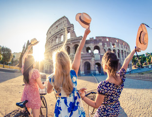Deurstickers Rome Three happy young women friends tourists with bikes waving hats at Colosseum in Rome, Italy at sunrise.