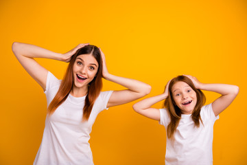 Portrait of cute impressed people with long haircut screaming wow omg wearing white t-shirt isolated over yellow background