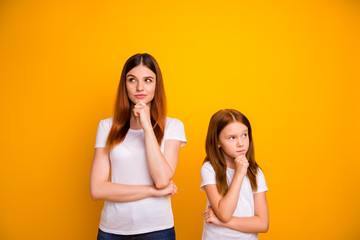 Portrait of minded ladies touching their chin having dreams isolated over yellow background