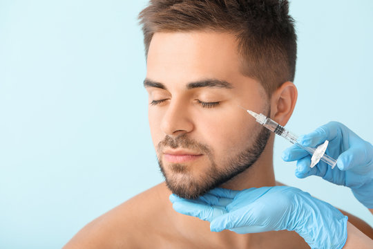 Handsome man receiving filler injection on color background