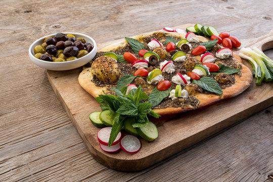 lebanese Manoushe ,bread of thyme topped with mint, reddish, and Labneh; Lebanese Zaatar Manouche; zaatar flat bread