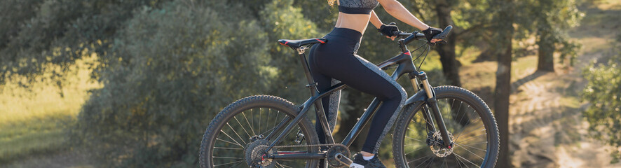 Girl on a mountain bike on offroad, beautiful portrait of a cyclist at sunset, Fitness girl rides a modern carbon fiber mountain bike in sportswear, a helmet, glasses and gloves.