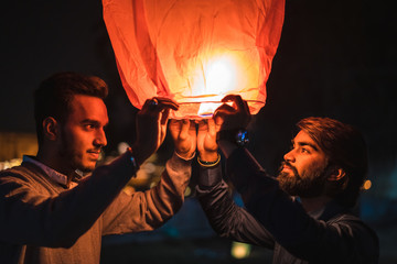 Indian Festival Diwali , Sky lantern. Two Indian young men launching a Chinese sky fly fire lantern to make a wish.