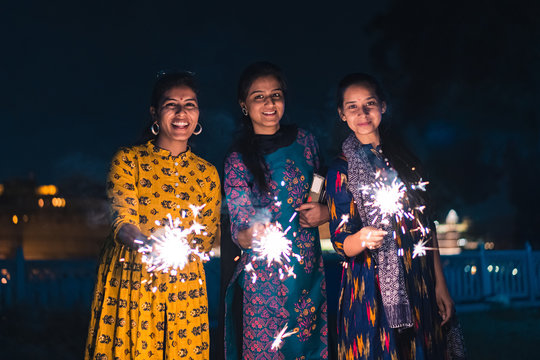 Three young Indian women with bengal fireworks, celebrating Indian Festival Diwali.
