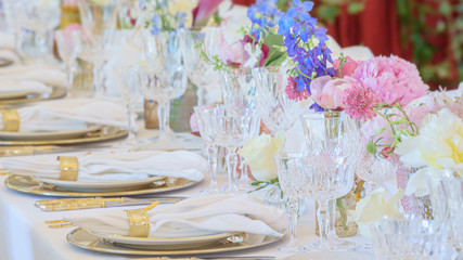 Elegant dinner table set with silverware, napkin and glass at restaurant before party