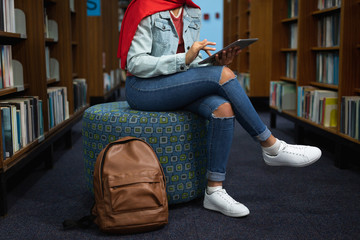 Young woman studying in library Wall mural