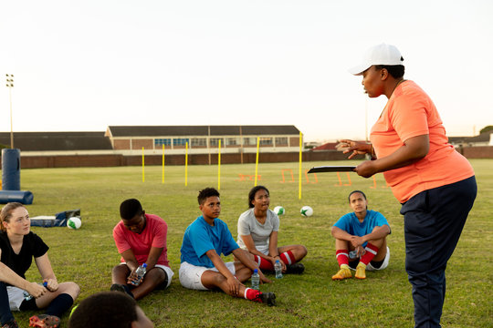 Young adult female rugby team and coach training
