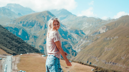 Woman hiking in mountains at sunny day time. View of Kazbegi, Georgia. Beautiful natural mountain background