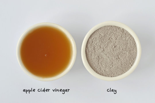 Homemade face mask made out of apple cider vinegar and clay on white background