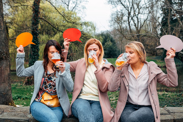 group of girls in the park drinking beer together while holding a thought bubble on their hands. Friendship and communication concept...