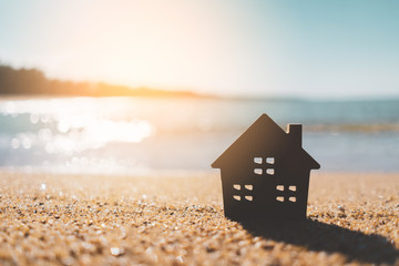 Small home model on sunset beach sand texture background.
