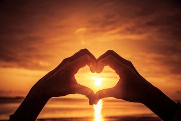 Hand als Herzform bei sonnenuntergang