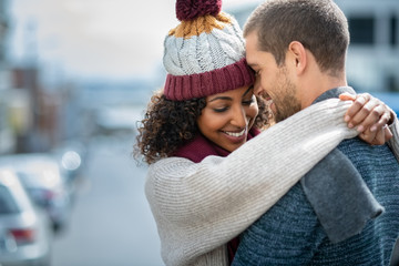 Happy couple in love embracing in winter
