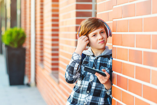 Portrait of schoolboy boy with modern hairstyle hair. Guy listens to music or watches video from his smart phone. New generation and technology concept.