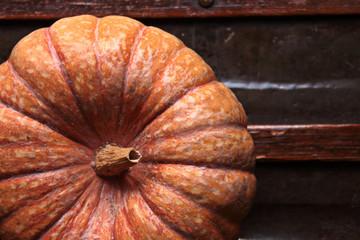 Calabaza de color naranja con texturas, sobre fondo de mueble antiguo, toma desde arriba, la imagen del fruto queda a la izquierda dejando espacio libre a la derecha.