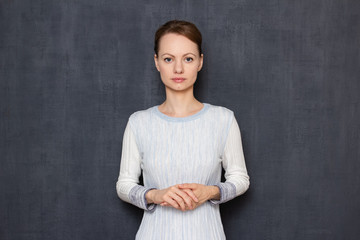 Portrait of calm and focused young woman waiting results