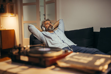 mid aged man listening music with headphones on record player, relaxed in sofa at his home