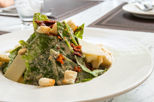 Cesar salad with bacon cheese on white plate in luxury restaurant.