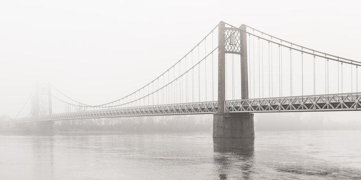 Suspension bridge over the Loire disappears on a foggy day, Ancenis, France
